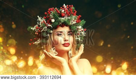 Beautiful happy young woman with a Christmas spruce wreath on her head, decorated with Christmas balls, berries and snowflakes. Green background. Copy space.