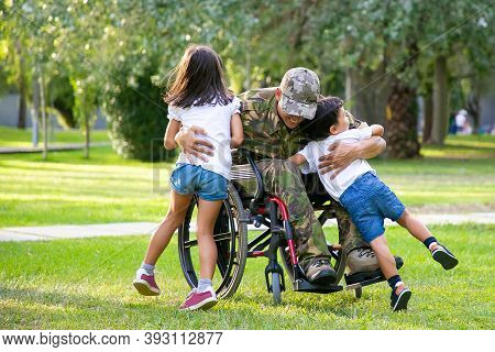 Happy Disabled Military Man In Wheelchair Returning Home And Hugging Kids. Veteran Of War Or Family