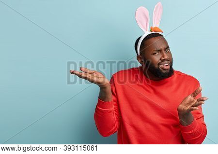 What Did You Say I Wonder. Puzzled Dark Skinned Man Has Indifferent Uncertain Facial Expression, Spr