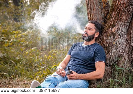 Modern Vape Man With Electronic Cigarette Out In The Forest. Electronic Cigarette.