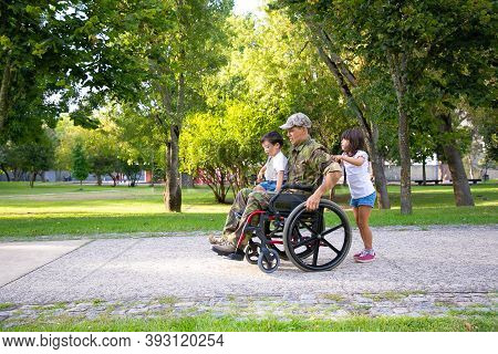 Handicapped Military Veteran Walking With Two Children In Park. Boy Sitting On Dads Lap, Girl Pushin