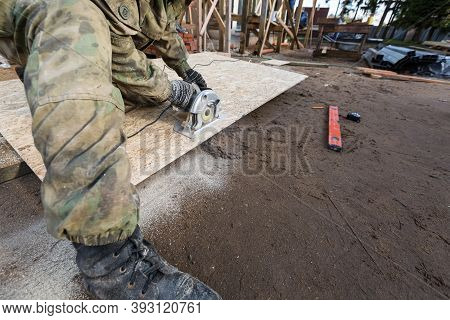 Construction Site. Construction Worker With Electrical Circular Saw Saws The Cement Particle Board O