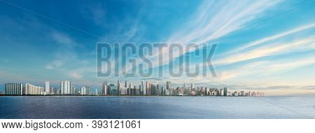 Panoramic City Landscape With Cloudy Blue Sky Over The Deep Blue Sea. Sunrise Over The Cityscape Vie