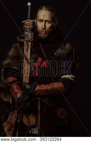 Portrait of a medieval knight in armour and with a sword over black background. Knight Templar. Historical reenactment.