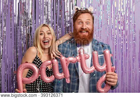 Joyous Couple Stand Next To Each Other, Have Fun Indoor, Pose In Decorated Photozone, Enjoys Spare T