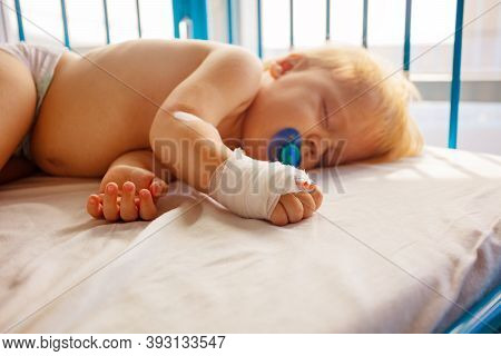 Close Photo Of A Small Toddler Sleep In Hospital With Catheter In His Hand And Pacifier