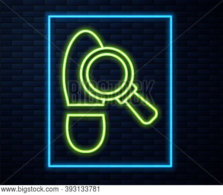 Glowing Neon Line Magnifying Glass With Footsteps Icon Isolated On Brick Wall Background. Detective