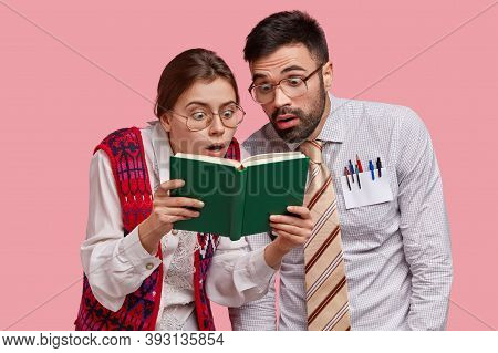 Stunned Nerds Stare At Opened Book, Read Astonishing Information, Wear Big Spectacles For Good Visio