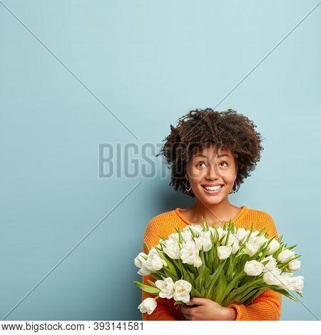 Vertical Photo Of Joyful Woman Gazes Upwards, Smiles Broadly, Holds White Tulips, Wears Jumper, Rejo