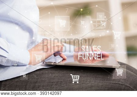 Young person makes a purchase through online shopping application with SALES FUNNEL inscription