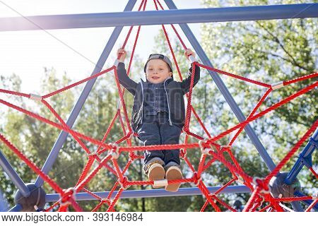 Happy Little Child Boy Climbed On Playground