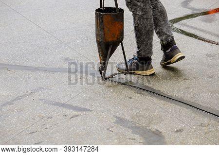 Workers Applying Blacktop Sealer To Asphalt A Road Protective Coat Restoration Work