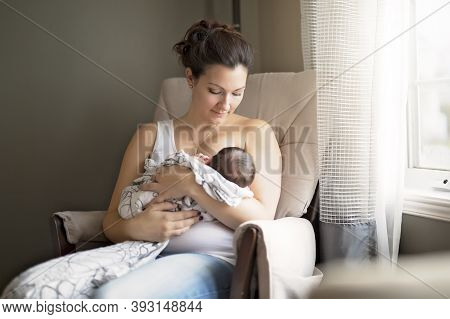Mother Breastfeeding Her Little Baby Boy In Arms.