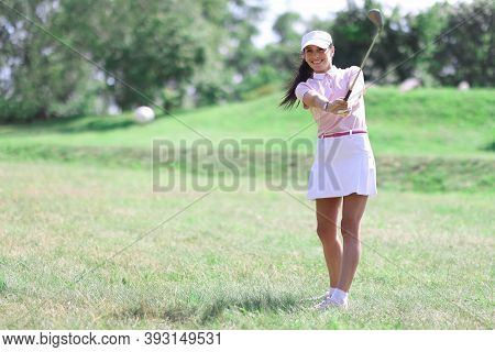 Female Golfer Hits The Ball With Club. Golfing As A Lifestyle Concept