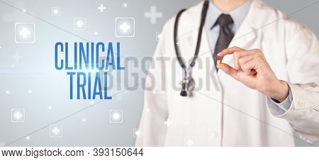 Close-up of a doctor giving a pill with CLINICAL TRIAL inscription, medical concept