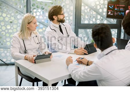 Cropped Side Angle View Of Multi-ethnic Group Of Young Doctors Sitting Around Table During Medical S