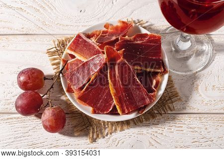 Sliced Jamon On A Plate, Few Pink Grapes And Wine Glass Over White Wood Table. Hard Light Shot. Trad