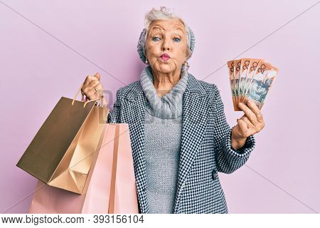 Senior grey-haired woman holding shopping bags and australia dollars puffing cheeks with funny face. mouth inflated with air, catching air.