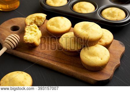 Homemade Cornbread Muffins On A Rustic Wooden Board On A Black Background, Side View. Close-up.