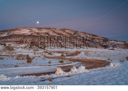 windy ranch road in Colorado mountain valley, fall evening after sunset, Red Mountain Open Space with fresh snow