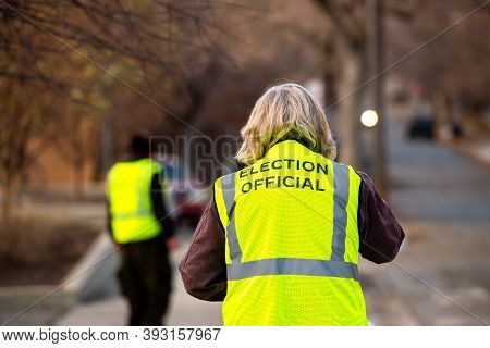 Helena, Montana / November 3, 2020: Gray Haired Woman Election Official From Behind, Helping Voters