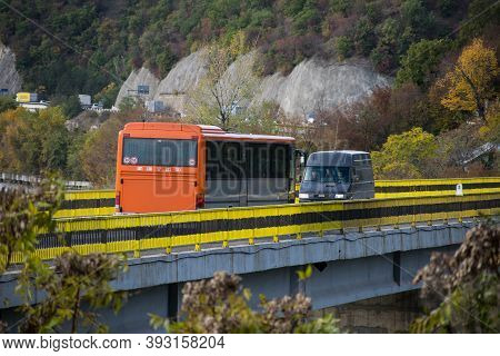 A Bus And A Van Cross The Bridge. Autumn On A Road Near The Mountain.romania, Severin. November, 02,