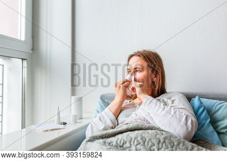 Sick Woman Blowing Her Nose With Headache And Fever Lying Under The Blanket. Sick Woman Staying In B