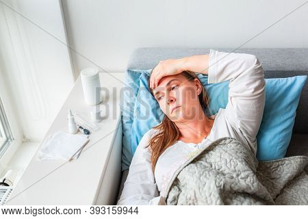 Sick Woman With Headache And Fever Lying Under The Blanket. Sick Woman Staying In Bed With Temperatu