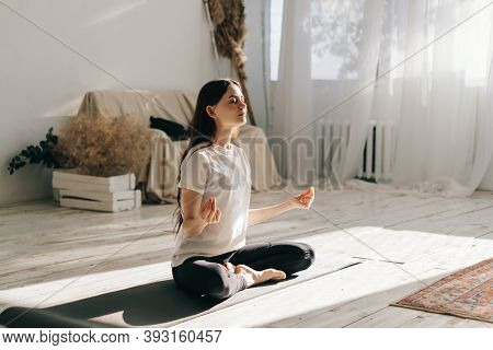 Beautiful Brunette Fitness Woman Meditate, Doing Yoga Indoors At Home. Staying Fit And Healthy