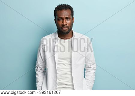 Image Of Sad Sorrowful Black Man With Thick Bristle, Wears White Shirt, Feels Troublesome, Looks At