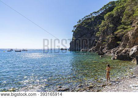 Pedrosa Cove With A Woman On The Seashore In Llafranc, Girona, Catalonia, Spain.