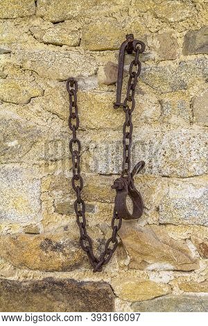 Stone Wall With Fixed Rusty Rundown Chains