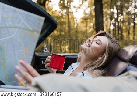 Happy Woman With Closed Eyes Holding Coffee And Road Atlas In Cabrio On Blurred Foreground