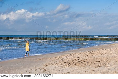 Boy In A Yellow Jacket Walks Along The Baltic Sea Coast, Beautiful Nature And A Child During A Holid