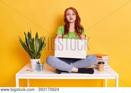 Pleasant Looking Caucasian Woman Using Laptop Sitting On Table Working Online Via Laptop Against Yel