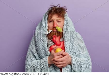 Photo Of Upset Sick Man Has Red Nose From Rhinitis, Trembles Under Coverlet, Warms With Hot Water Ba