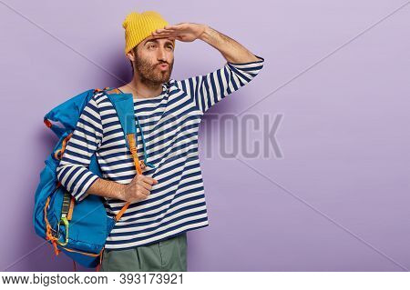 Serious Backpacker Keeps Lips Folded, Looks Far Away With Hand On Forehead, Carries Blue Rucksack On