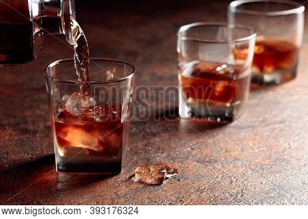 Pouring Whiskey In Glass With Natural Ice. Dammed Glass  With Strong Alcoholic Drink.
