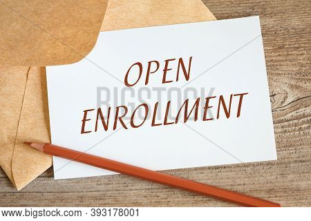 Open Craft Envelope And Card With The Words Open Enrollment, Pencil On A Wooden Surface.