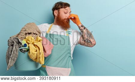 Foxy Bearded Man Closes Nose With Fingers From Unpleasant Smell, Collects All Dirty Laundry, Wears C