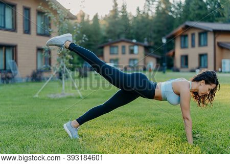Fitness Woman Stands In Plank, Raises Legs And Does Fitness Exercises, Dressed In Active Wear, Shows