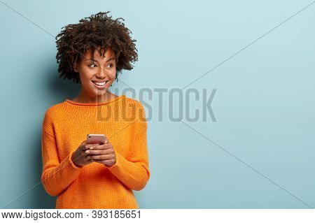 Photo Of Cheerful Delighted African American Woman Types Sms On Modern Cell Phone Device, Enjoys Goo