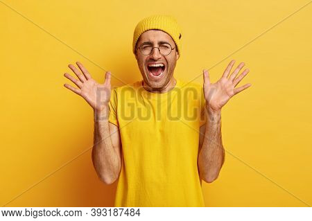 Handsome Youngster Screams With Negative Emotions, Has Eyes Closed, Raises Palms, Keeps Mouth Widely