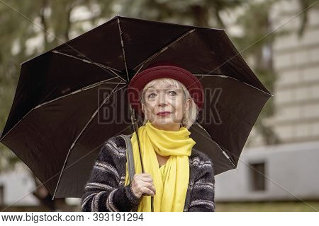 Street Portrait Of An Elderly Woman 60-65 Years Old In A Hat Under An Umbrella On The Background Of