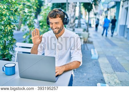 Handsome man with beard wearing casual white shirt on a sunny day working using laptop and wearing headphones and waving to videocall at cafeteria