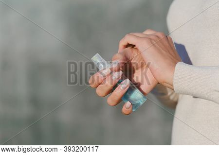 Hand Disinfection With Antiseptic. Against The Background Of A Gray Concrete Wall.