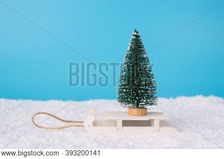 Merry Christmas Concept. Closeup Photo Of Small Toy Christmas Tree Standing On Wooden Retro Sledges