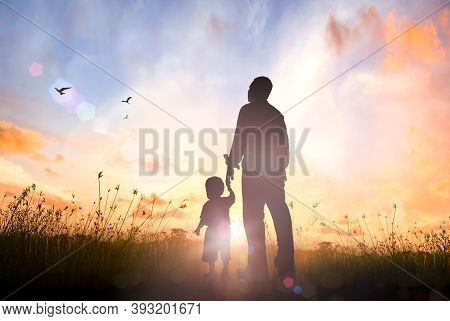 Happy Father's Day Concept: Silhouette Father And Son Standing On Meadow Autumn Sunrise Background