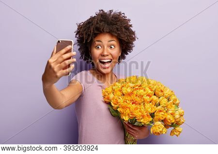 Excited Overjoyed Dark Skinned Woman Takes Selfie With Smartphone, Holds Tulip Bouquet, Being Very G