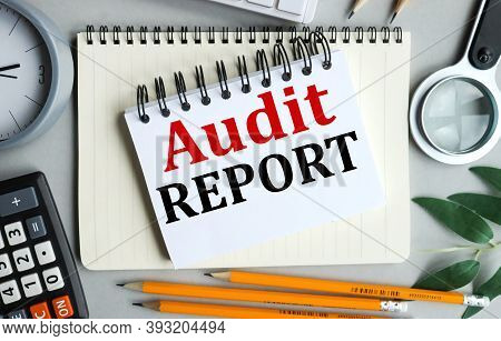 Audit Report, Text On White Notepad Paper On Gray Background Near Calculator